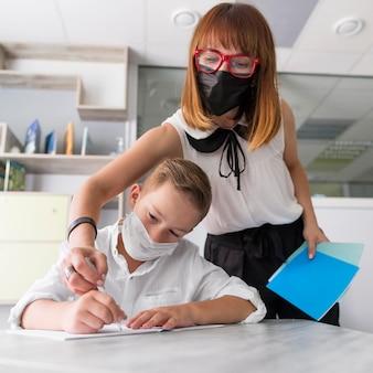 Professora ajudando seu aluno na aula