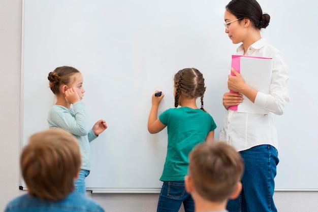 Professora ajudando seus alunos com o que escrever em um quadro branco