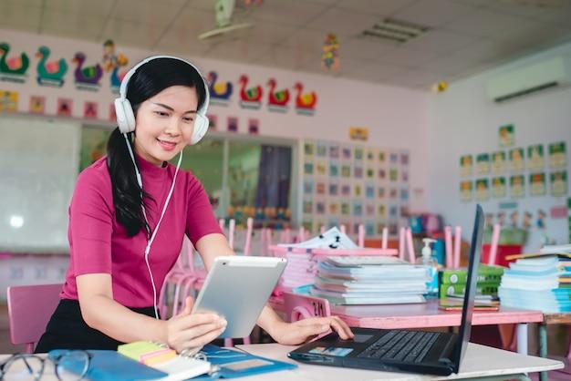 Professora asiática do jardim de infância está ensinando online alunos do jardim de infância. professores e alunos usam sistemas de videoconferência online para ensinar os alunos.