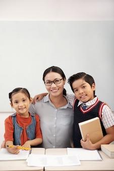 Professora asiática em copos posando em sala de aula com alunos de menino e menina