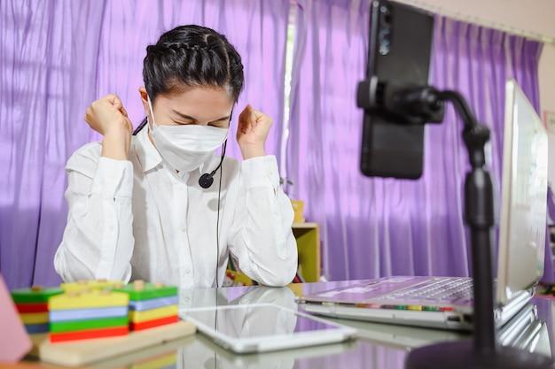 Professora asiática pensando muito e estressada sentada triste ela usa uma máscara enquanto estudava online. vídeo online para educação