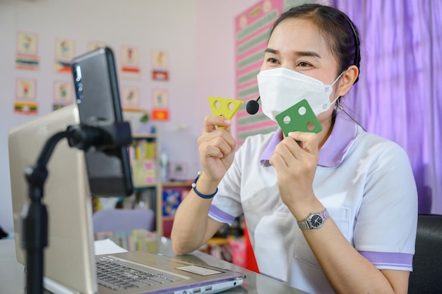 Professora asiática usando máscara está ensinando alunos a estudar online por meio de uma tela de computador usando um sistema de videoconferência online para educação
