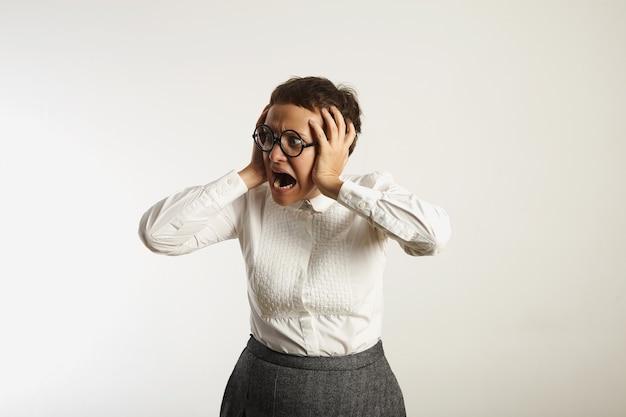 Professora assustada segura a cabeça entre as mãos e grita de horror na parede branca