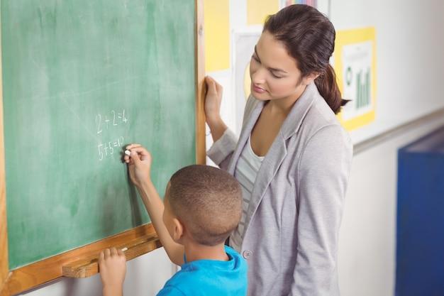 Professora bonita, ajudando o aluno na lousa