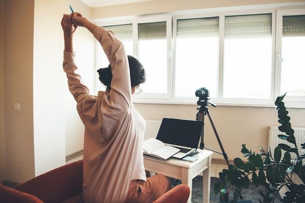 Professora branca pronta para as aulas online no computador com um livro e uma câmera moderna na frente