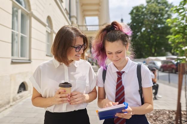Professora caminhando e falando com uma xícara de café e estudante adolescente, garota buscando conselhos de um tutor