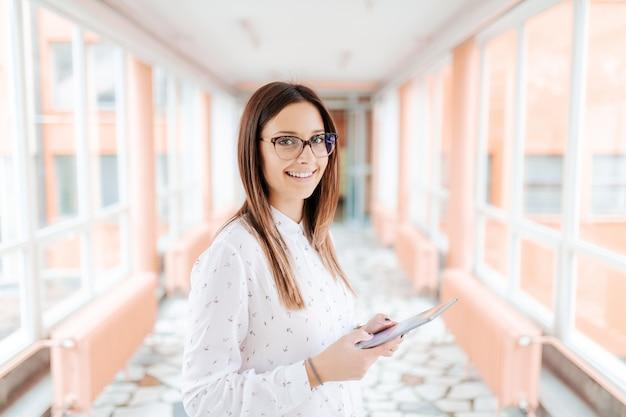 Professora caucasiana com óculos usando tablet e olhando para a câmera em pé no corredor