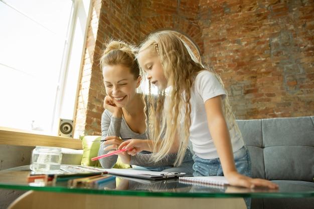 Professora caucasiana feminina e menina, ou mãe e filha. educação escolar em casa
