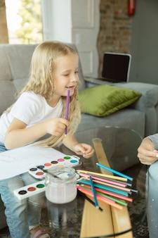 Professora caucasiana feminina e menina, ou mãe e filha.