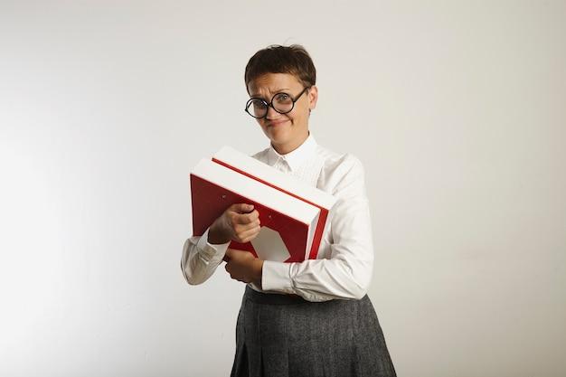 Professora cética, vestida de maneira conservadora e segurando pastas pesadas brilhantes em branco