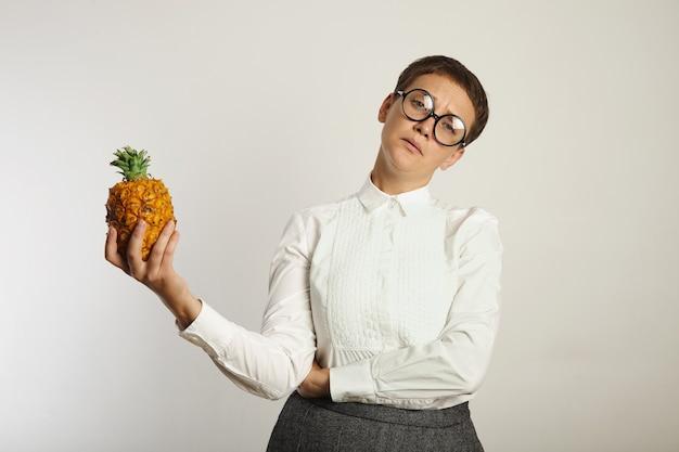 Professora com ar cansado em uma blusa branca, saia cinza e óculos pretos redondos segura um pequeno abacaxi na parede branca