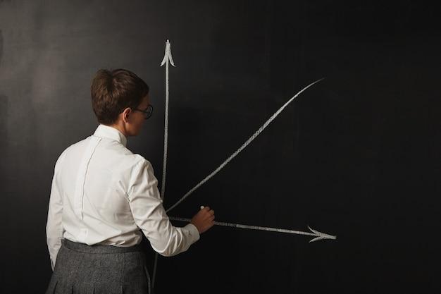 Professora com cabelo curto na blusa branca e saia cinza desenhando um gráfico no quadro negro
