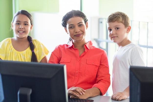 Professora com crianças na aula de informática