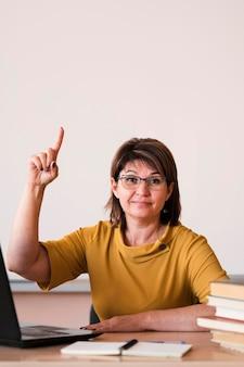 Professora com laptop apontando acima da cabeça