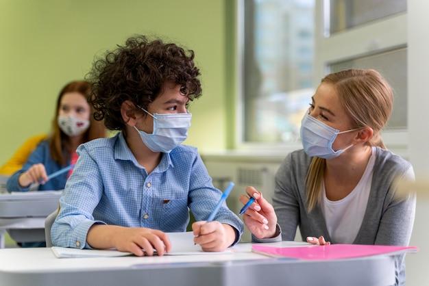 Professora com máscara médica ajudando alunos em sala de aula