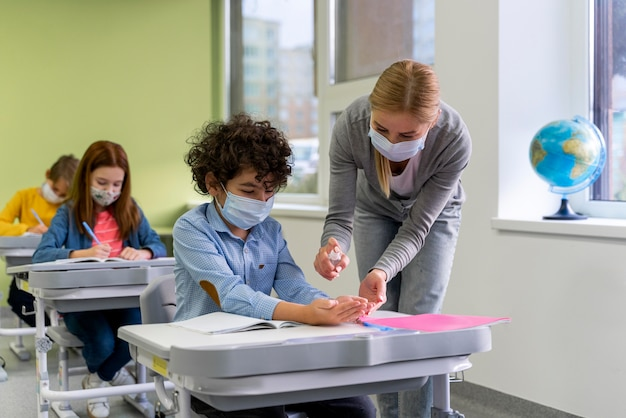 Professora com máscara médica dando desinfetante para as mãos para crianças na sala de aula