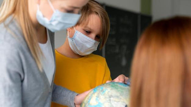 Professora com máscara médica ensinando geografia com o globo na sala de aula