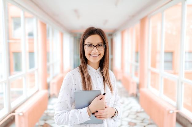 Professora com óculos e cabelos castanhos, segurando o tablet nos braços em pé no corredor