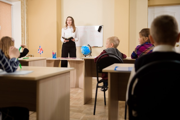 Professora dando aula para alunos do ensino fundamental.