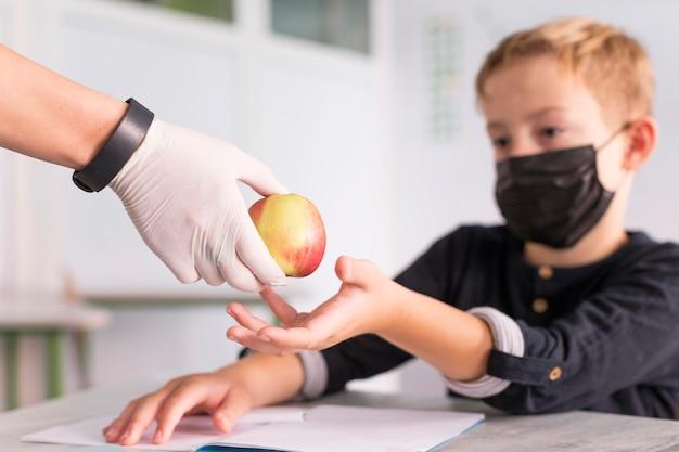 Professora dando uma maçã para seu aluno