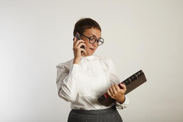 Professora de blusa branca e saia cinza olha para o grande livro que ela segura enquanto fala em seu telefone celular isolado no branco