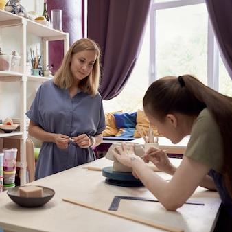 Professora de cerâmica olhando para uma jovem aprendiz fazendo cerâmica na oficina