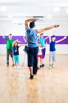 Professora de dança dando aula de fitness para crianças