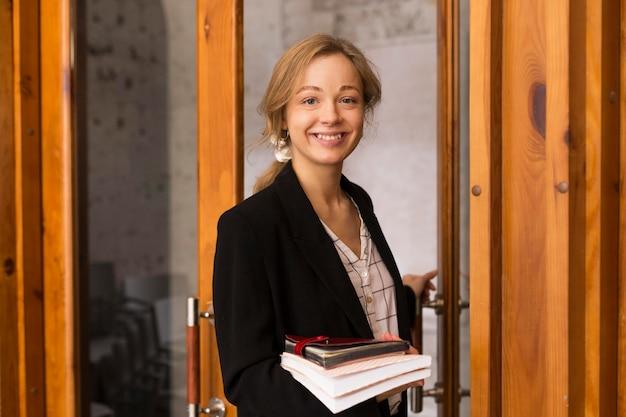 Professora de frente com pilha de livros