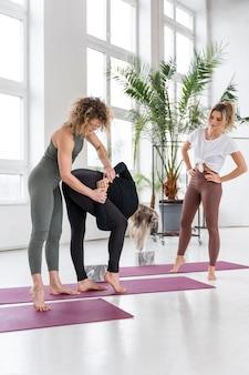 Professora de ioga completa ajudando mulher