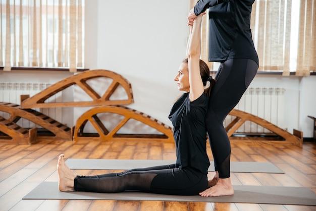 Professora de ioga está ajudando uma jovem a fazer poses na academia