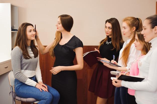 Professora de maquiagem com suas alunas. lição do tutorial de maquiagem