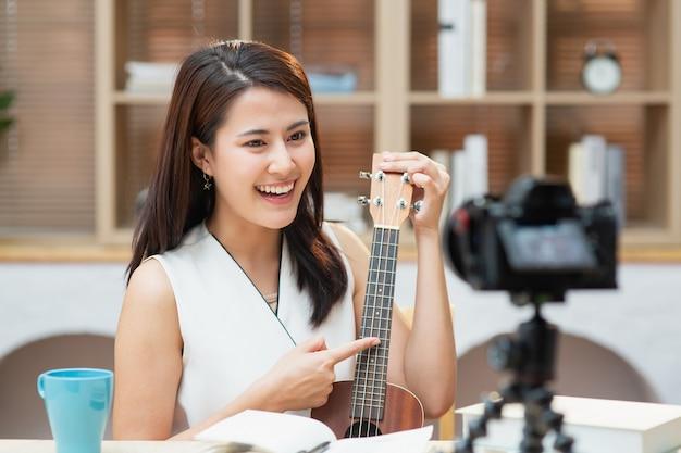 Professora de música asiática sentada na sala de estar conversando com a câmera e ensinando violão em casa