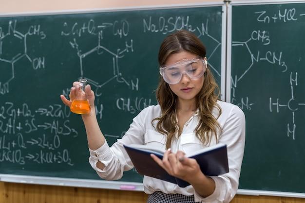 Professora de química segura um frasco com um líquido laranja e realiza um experimento científico em sala de aula. ciência