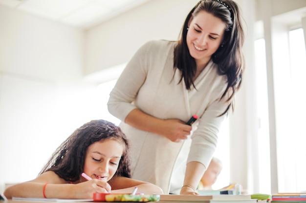 Professora de sexo feminino inclinada sobre a aluna