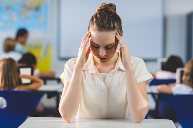 Professora deprimida, tocando sua cabeça