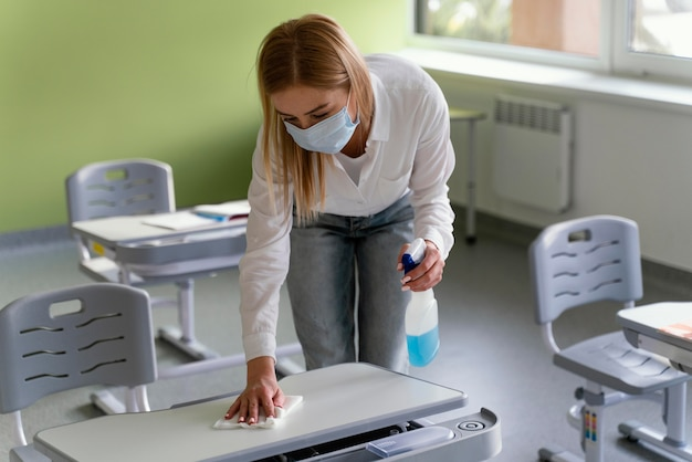 Professora desinfetando bancos escolares em sala de aula