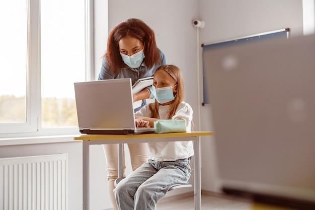Professora e aluna com máscaras usando tablet em sala de aula