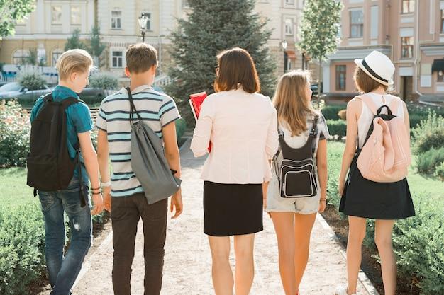 Professora e grupo de adolescentes estudantes do ensino médio