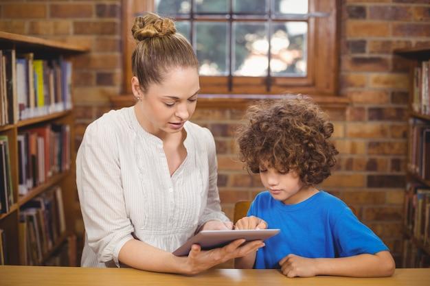 Professora e pupila loira usando tablet na biblioteca