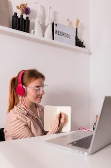 Professora em casa dando uma aula online e mostrando a lição aos alunos