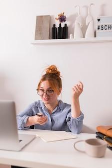 Professora em casa explicando aula durante uma aula online