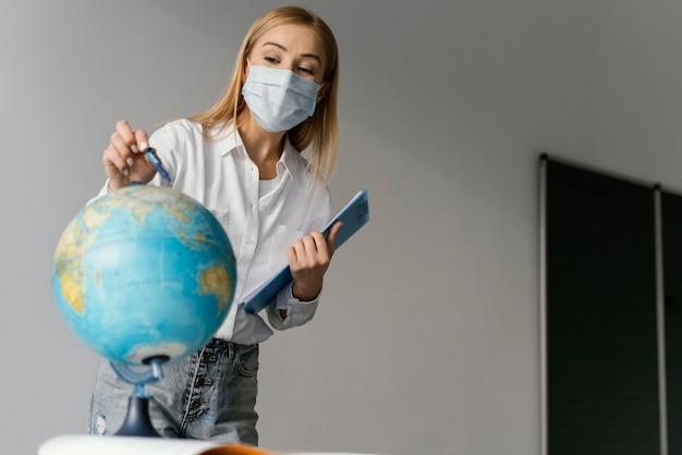 Professora em sala de aula com a prancheta apontando para o globo