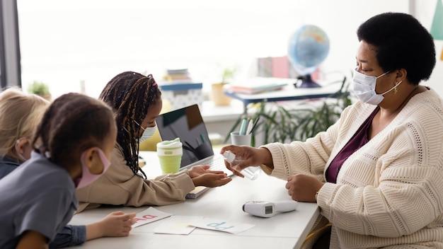 Professora ensinando crianças sobre desinfecção