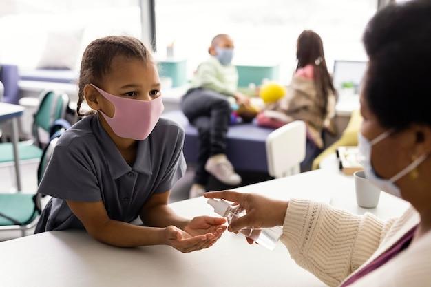 Professora ensinando crianças sobre desinfecção Foto gratuita