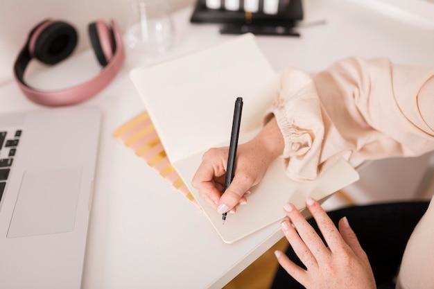 Professora escrevendo algo na agenda durante a aula online