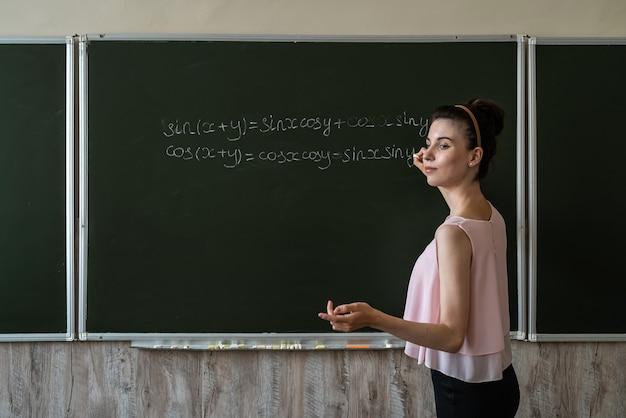 Professora escrevendo fórmulas de matemática, cos e pecado. conceito de educação