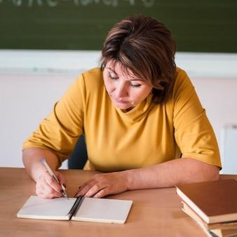 Professora escrevendo na mesa