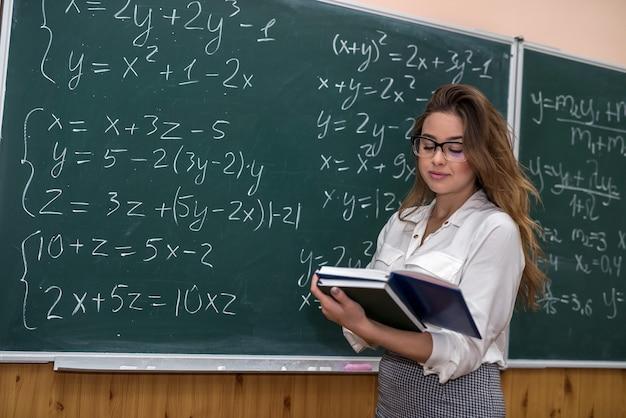 Professora escreveu fórmulas matemáticas na lousa e explicou uma lição. escola