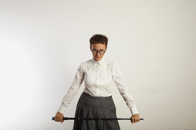 Professora estrita, vestida de maneira conservadora e com um longo ponteiro preto na parede branca