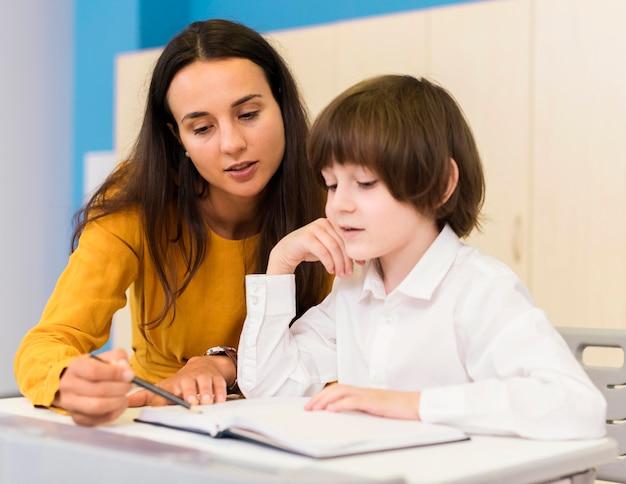 Professora explicando a lição para seu aluno